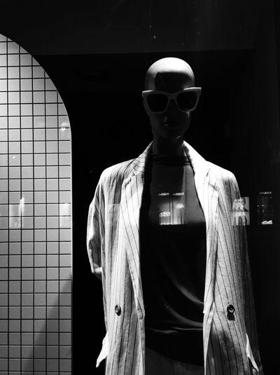 Man wearing sunglasses standing by window