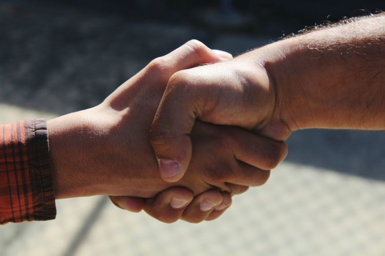 Cropped image of men shaking hands outdoors