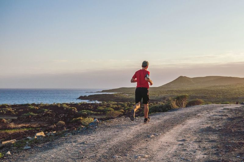 Rear view of man running on dirt road on coastline against sky