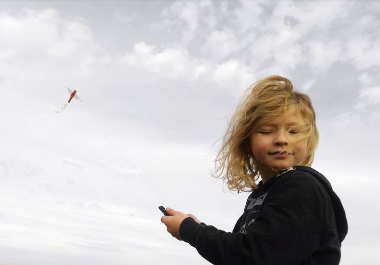 Low angle view of boy flying kate against sky
