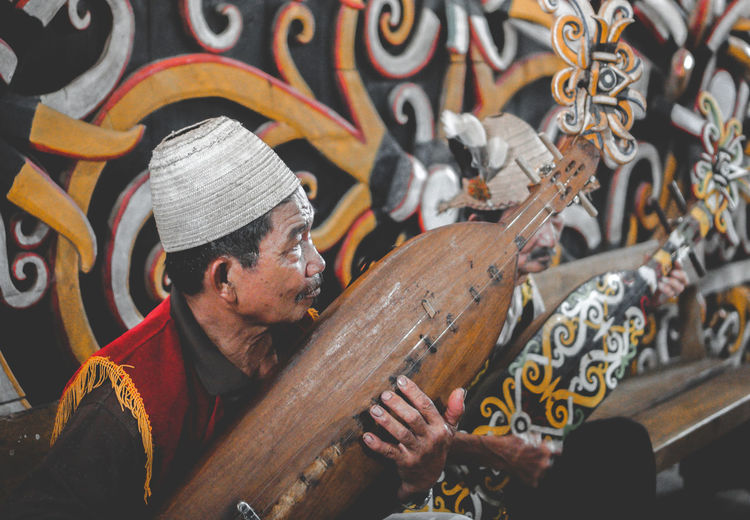 Man working on wood with musician dayaknese