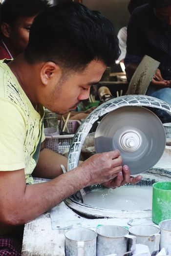 Side view of man with grinder working at workshop