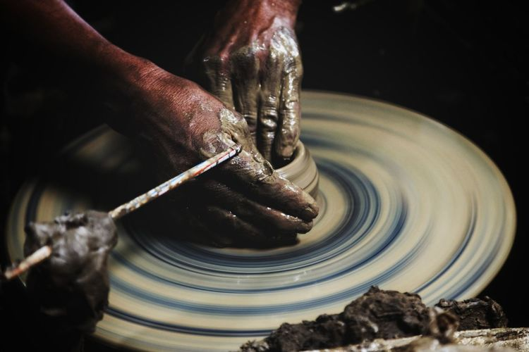 Cropped Image Of Man Shaping Earthenware On Pottery Wheel At Workshop