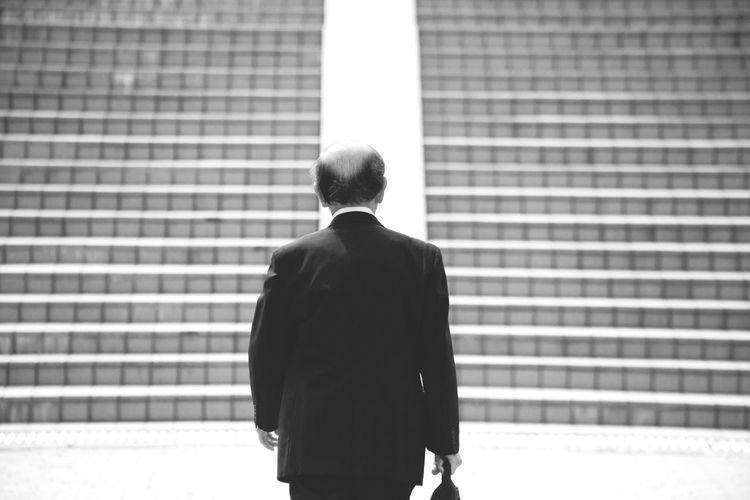Rear View Of Businessman Walking Towards Steps