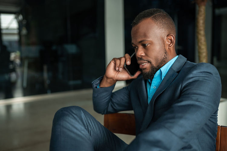 Businessman wearing suit talking on phone while sitting at office