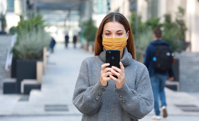 Portrait of man holding smart phone on street