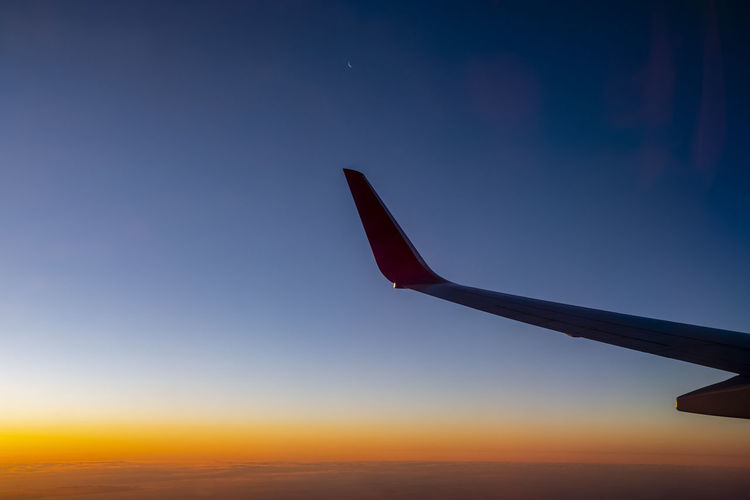 Airplane flying against sky during sunset