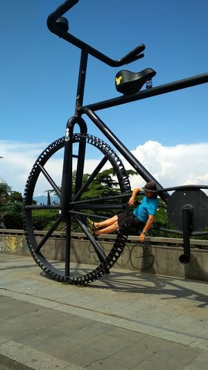 Low angle view of boy cycling against sky