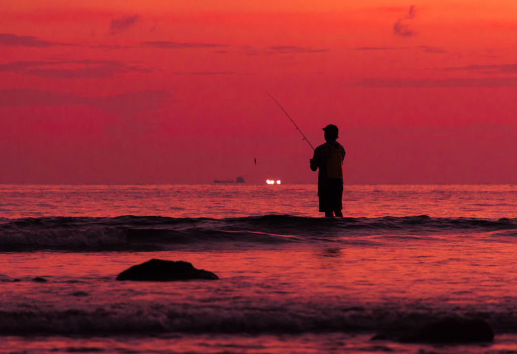 Silhouette man fishing in sea against orange sky
