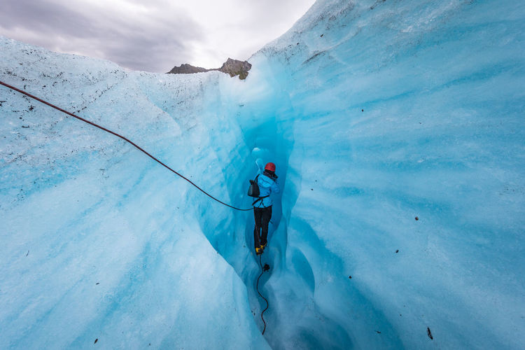 Rear view of person walking in ice cave