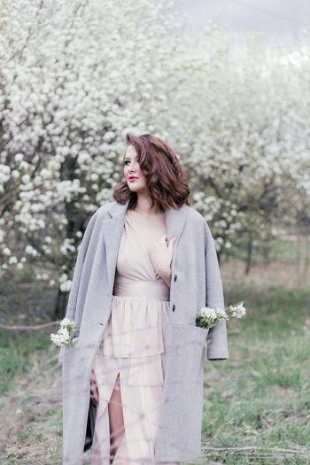 Beautiful girl in a dress walking in a blooming garden