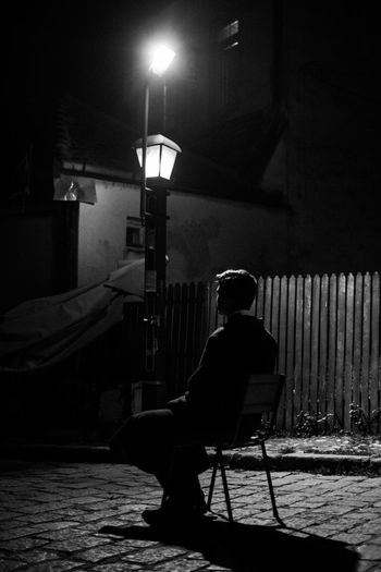 young man sitting on a chair in a street Architecture Building Exterior Built Structure Chair Full Length Illuminated Leisure Activity Lifestyles Lighting Equipment Men Nature Night One Person Real People Relaxation Seat Side View Sitting Street