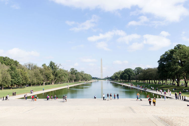 People by reflecting pool with washington monument in background
