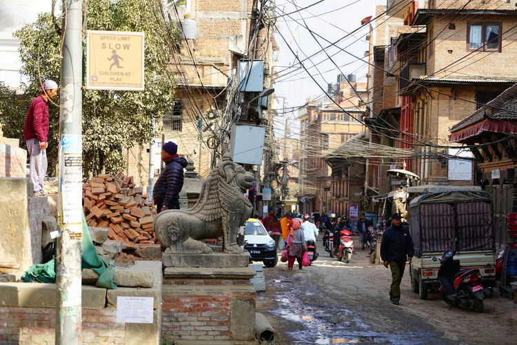 People working on street amidst buildings in city