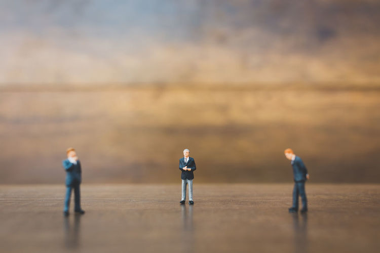Figurines Of Businessmen On Wooden Table