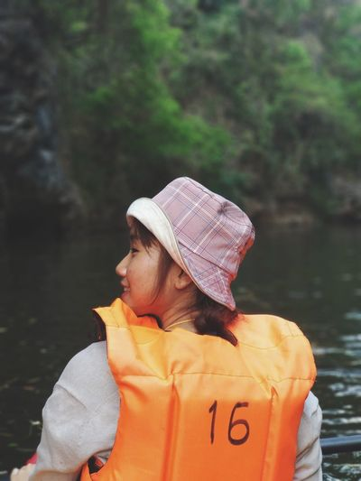 Rear view of woman with life jacket in river against trees