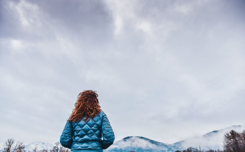 Rear view of woman with umbrella against sky during winter