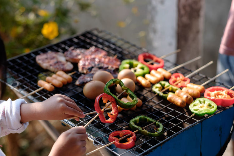 Cropped Image Of Girl Cooking Food On Barbecue In Yard
