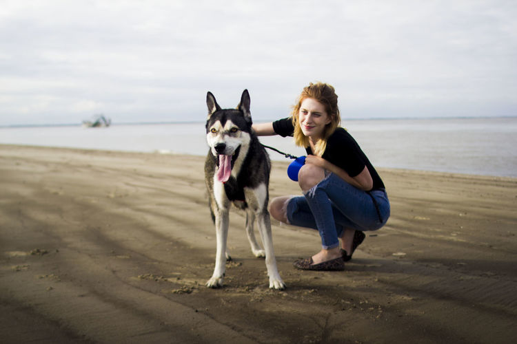 Portrait of woman with dog on beach against sky