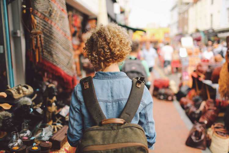 Backpack Blonde Brighton Casual Clothing City City Life Curly Hair Day Focus On Foreground Girl Hat Leisure Activity Lifestyles Market Market Outdoors Selective Focus Shops Warm Clothing Break The Mold Let's Go. Together. Breathing Space Your Ticket To Europe Connected By Travel