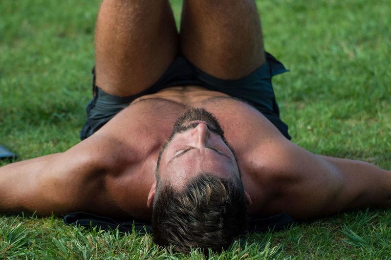 Shirtless man exercising on grass at park