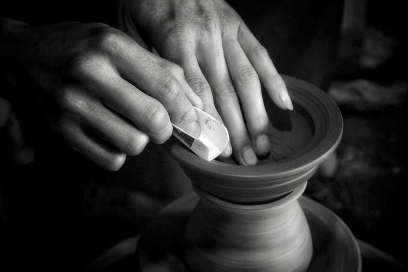 Cropped hands shaping pottery in darkroom