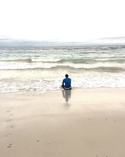 Rear view of man sitting on beach against clear sky