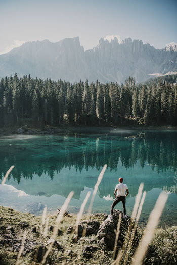 Man standing by lake against mountains