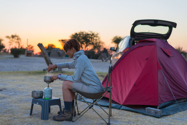 Woman Cooking With Camping Stove While Sitting By Tent During Sunset Against Sky
