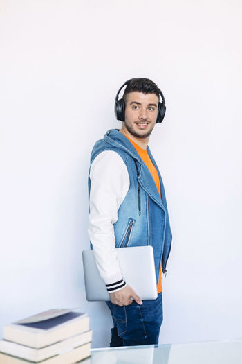 Side View Young Man Standing Holding Lifestyle Trendy Looking Away Adult Millennial Modern Stylish person Teacher Relaxed Tablet Notebook Smart Casual Confident  Male Beard Fashionable Headphones Handsome White Background Device Full Length Isolated Fashion Successful Guy Profile People Casual Studio Carrying Men Contract Model Finance Earphones Earbuds One Person Studio Shot Young Adult Indoors  Young Men Front View Casual Clothing Clothing