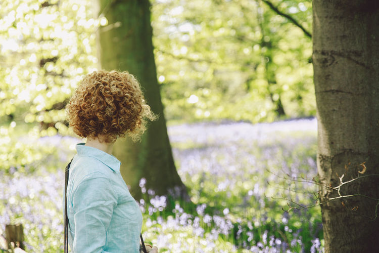 Side view of woman looking at plants at forest