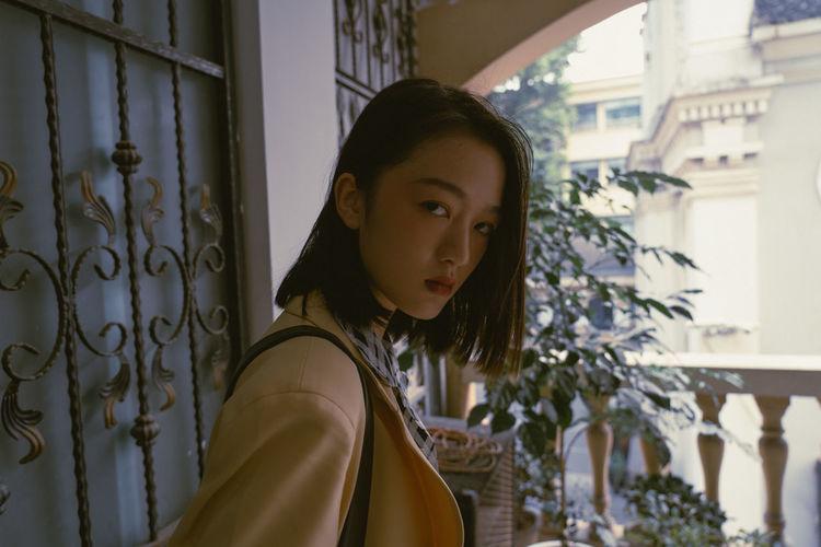 Portrait of woman standing against window