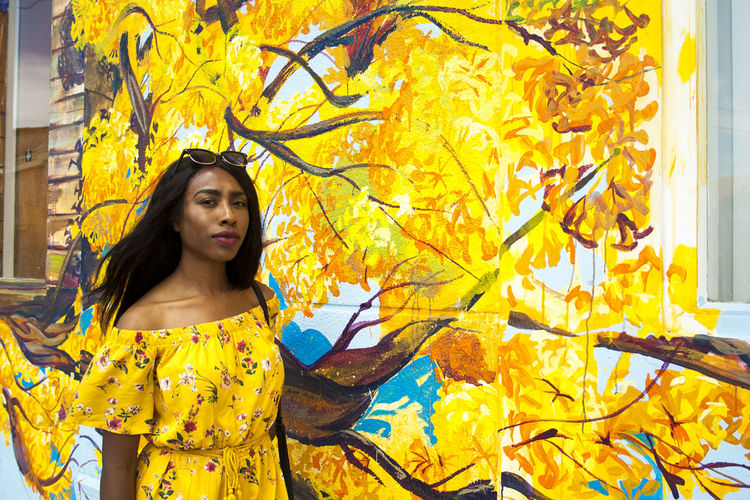 Portrait of young woman standing against yellow flowers