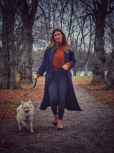 Woman walking dog on footpath amidst trees