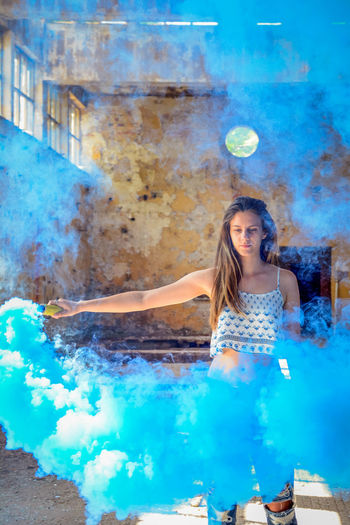 Portrait of young woman holding smoke bomb