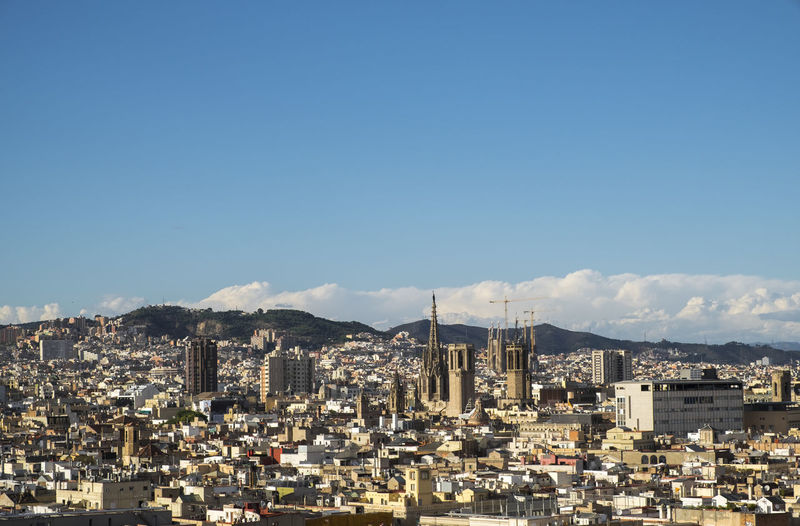 Distant view of sagrada familia in city against sky