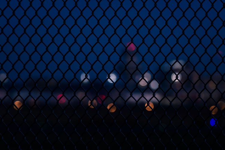 Chainlink fence against airport building at night.