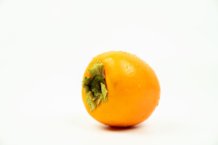 exotic kaki fruit, lying down on his side. Isolated on a white background. Studio Shot Food And Drink Healthy Eating Food White Background Single Object Wellbeing Freshness Copy Space Indoors  Cut Out Still Life Close-up Fruit Orange Color Yellow Kaki Exotic Fruits Japanese Food Diet Vitamins Raw Fresh