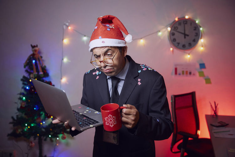 Curious businessman wearing santa hat holding laptop and coffee cup against illuminated christmas tree and lights at home