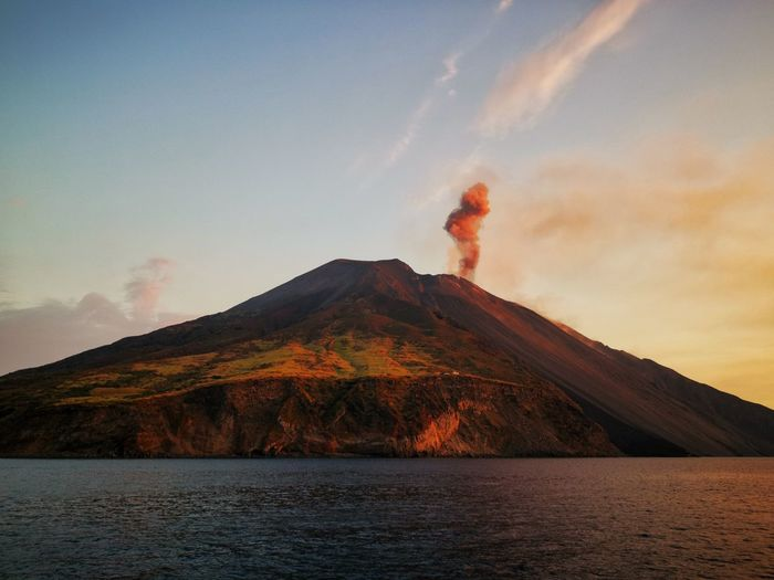 Scenic view of volcanic mountain by sea against sky during sunset