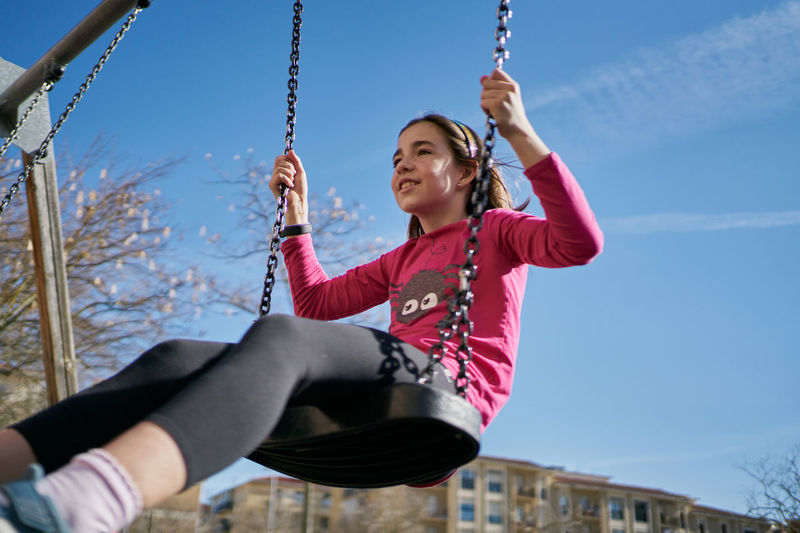 Low angle view of smiling girl on swing at playground