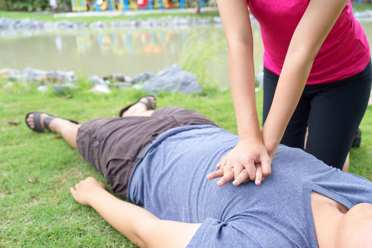 Midsection of woman giving cpr to unconscious victim lying on field