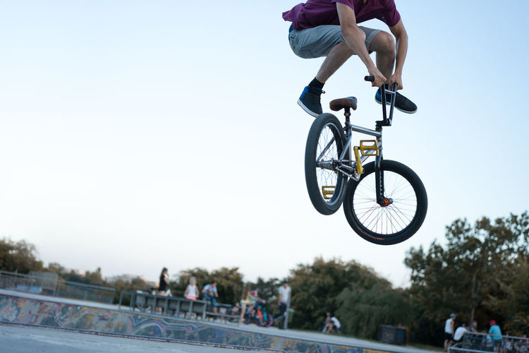 Low section of man with bicycle performing stunt against clear sky