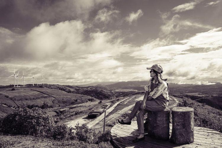 Woman sitting on tree stump on field against sky