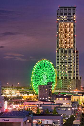 Illuminated ferris wheel in city against sky