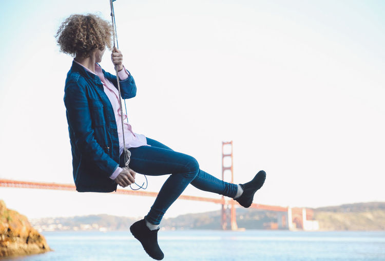Bay Area California Golden Gate Bridge San Francisco Swinging Bay Bridge Bridge - Man Made Structure Casual Clothing Clear Sky Curly Hair Day Focus On Foreground Full Length Girl Lifestyles Motion One Person Outdoors People Real People Sky Swing Young Adult Young Women California Dreamin