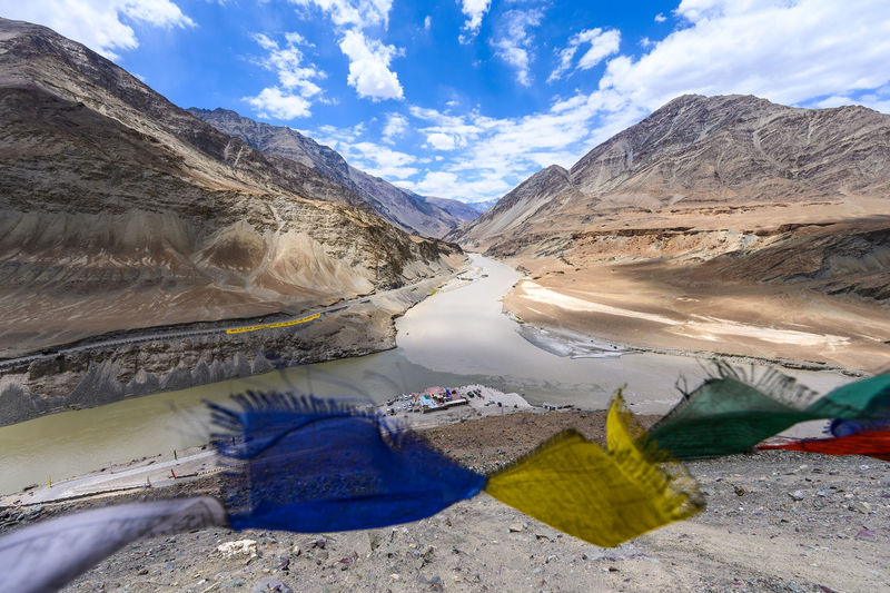 Scenic view of prayer flag by river and mountains against sky