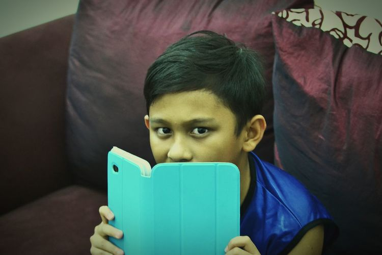 """""""Hide My Face"""". Aha...... there you are with your turquoise tab. Smile, Kid...... Turquoise By Motorola"""