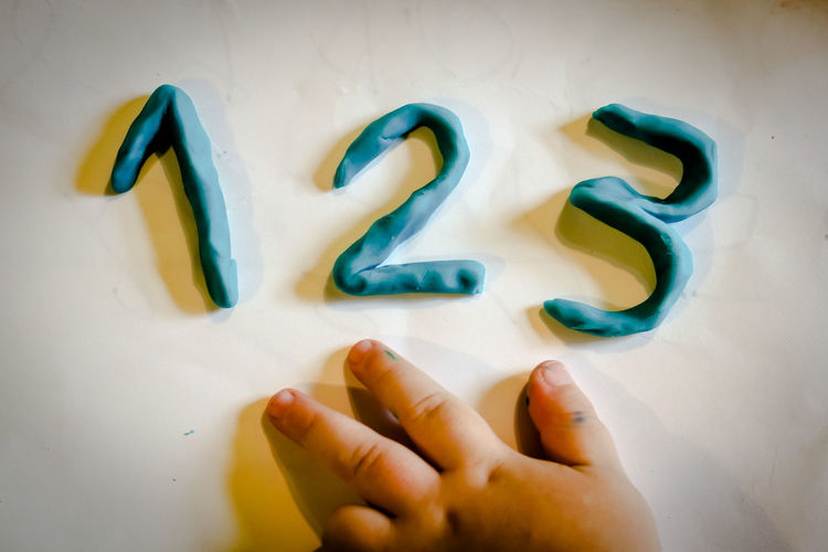Hand of a Preschool Child Learning the 123 on a table Education