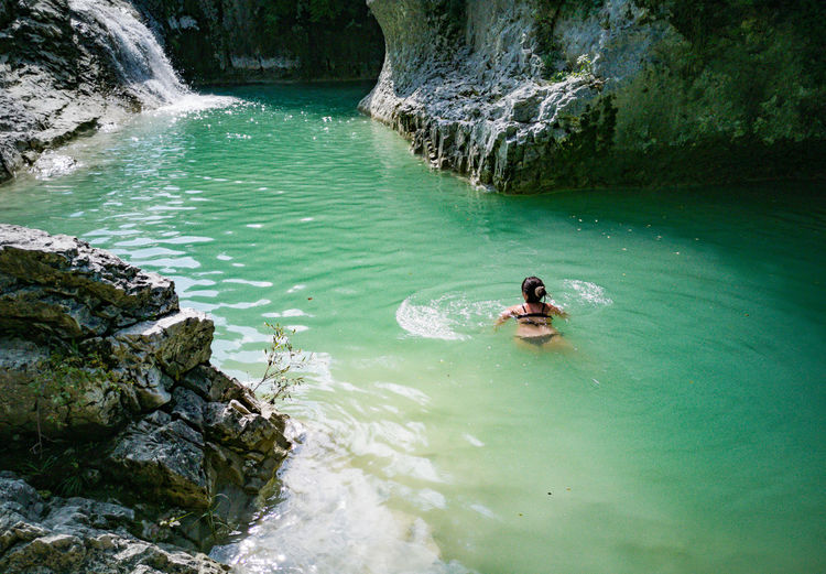 Woman swimming in green river pool. nature, outdoors, idyllic, vacation.